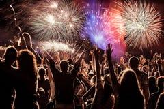 Menigte het letten op vuurwerk bij Nieuwjaar stock foto's