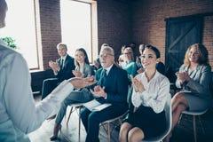 Menigte van aardige vrolijke in elegante specialistendeskundigen die klassencursussen bijwonen die bij de economie van de coacher stock foto