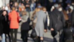 Menigte van anonieme mensen die op bezige straat lopen