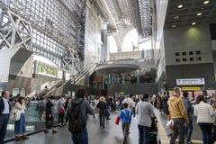 Menigte van mensen bij passagierssamenkomst binnen de de Postbouw van Kyoto, het belangrijkste station en de vervoershub in Kyoto Stock Afbeeldingen
