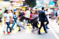 Menigte van mensen die een straat in Hongkong kruisen Stock Afbeeldingen