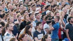 Menigte van mensen die op de uitzending van de voetbalwedstrijd op een vierkant letten Voorraadlengte Voetbalventilators stock videobeelden