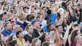 Menigte van mensen die op een vierkant tijdens de uitzending van de voetbalwedstrijd dansen Voorraadlengte Voetbalventilators stock footage