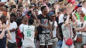 Menigte van mensen die op een vierkant tijdens de uitzending van de voetbalwedstrijd dansen Voorraadlengte Voetbalventilators stock videobeelden