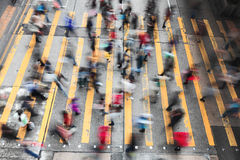 Menigte van mensen die op gestreepte kruisingsstraat lopen Stock Foto's