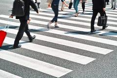 Menigte van mensen die op gestreepte kruisingsstraat lopen Stock Foto