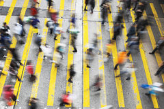 Menigte van mensen die op gestreepte kruisingsstraat lopen stock fotografie