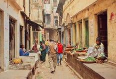 Menigte van mensen die op smalle straat met voedselverkopers en kleine plantaardige opslag lopen Royalty-vrije Stock Afbeeldingen