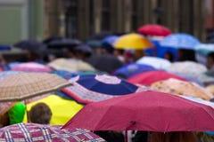 Menigte van mensen met paraplu's Stock Foto