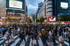 Menigte van mensen op beroemde Shibuya die in Tokyo bij nacht kruisen Stock Foto's