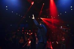 Menigte van mensensilhouetten bij de partijfestival van de nachtclub met rode lasers stock foto