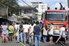 menigte van nieuwsgierige mensen die op de huisbrand letten die binnenlandse barakhuizen uithaalde royalty-vrije stock foto