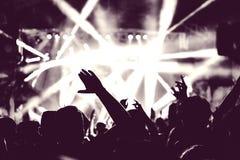 Menigte van publiek met handen bij een muziekfestival dat wordt opgeheven stock afbeeldingen