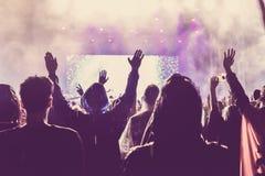 Menigte van publiek met handen bij een muziekfestival dat wordt opgeheven royalty-vrije stock afbeeldingen