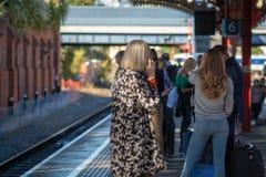 Menigte van vertraagde mensen die op treinlijn wachten zonder enig teken van trein royalty-vrije stock fotografie