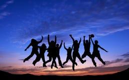 Menigte van vrienden die op blauwe hemelachtergrond springen stock afbeeldingen