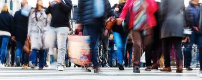 Menigten van mensen in motieonduidelijk beeld die een stadsstraat kruisen royalty-vrije stock foto's