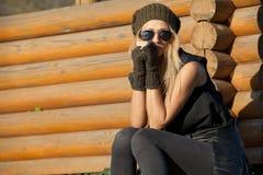 A menina à moda é poço de madeira próximo triste Fotos de Stock