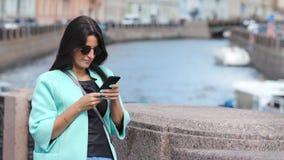Menina à moda adorável que toma a foto usando o smartphone da terraplenagem na arquitetura da cidade histórica filme