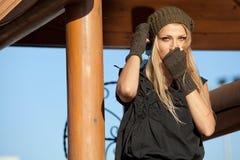 A menina à moda aquece as mãos perto do poço de madeira Fotografia de Stock