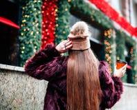 Menina à moda bonita nova do traseiro, posição no fundo das montras que realizam nas mãos do café para ir Foto de Stock Royalty Free