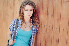 Menina à moda com os dreadlocks no fundo de madeira da parede Foto de Stock