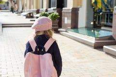 A menina à moda com trouxa, em um revestimento e a boina francesa correm à escola Vista traseira Imagens de Stock