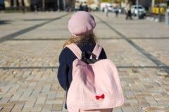 A menina à moda com uma trouxa, em um revestimento e a boina francesa correm à escola Fotos de Stock