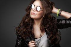 Menina à moda consideravelmente nova no casaco de cabedal e em óculos de sol redondos Fotografia de Stock Royalty Free