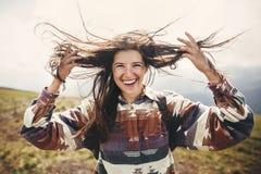 Menina à moda do moderno com trouxa e cabelo ventoso que sorri sobre montanhas Retrato da jovem mulher feliz que relaxa carefree fotografia de stock royalty free