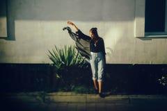 Menina à moda do moderno que levanta na luz ensolarada na rua, momento atmosférico Mulher fresca elegante em calças de brim da sa fotografia de stock royalty free