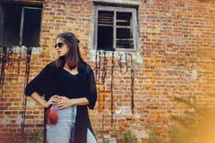 Menina à moda do moderno que levanta na rua, momento atmosférico Mulher fresca elegante em óculos de sol pretos e nas calças de b fotografia de stock