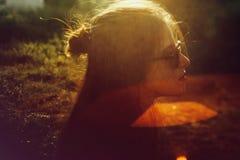 Menina à moda do moderno que levanta no parque ensolarado com feixes de surpresa do sol, momento atmosférico Retrato da mulher el imagens de stock