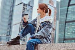Menina à moda do moderno do ruivo com tatuagem em seu revestimento vestindo da sarja de Nimes da cara que guarda o café afastado  imagens de stock royalty free