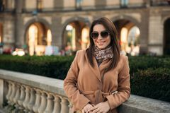 Menina à moda no revestimento que levanta para o fotógrafo perto do parque grande tempo ensolarado e modelo bonito foto de stock