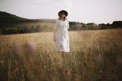 Menina à moda no vestido de linho que anda entre ervas e wildflowers no prado ensolarado nas montanhas Mulher de Boho que relaxa  fotos de stock royalty free