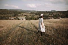 Menina à moda no vestido e no chapéu de linho que anda entre ervas e wildflowers no campo ensolarado nas montanhas Mulher de Boho fotos de stock royalty free