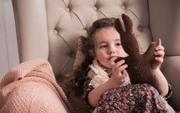 A menina à moda pequena joga com uma lebre A atmosfera morna do inverno imagem de stock royalty free