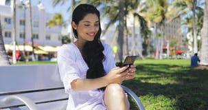 Menina à moda segura que usa o telefone no parque vídeos de arquivo