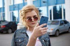 Menina à moda vestida nova bonita que anda em torno da cidade, tomando um selfie imagem de stock