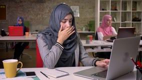 A menina árabe bonita cansado de bocejo está usando seu portátil ao sentar-se no desktop, colegas no fundo, senhoras modernas filme