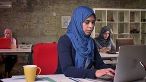 Menina árabe de trabalho bonita esperta em escuro - o hijab azul está sentando-se em desktop e está datilografando-se em seu comp vídeos de arquivo