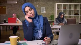 A menina árabe impressionante focalizada é concentrada na conversa telefônica ao sentar-se em seu desktop atrás do computador e filme