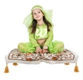 Menina árabe pequena que senta-se em um tapete de vôo imagem de stock