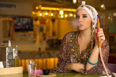 Menina árabe que guarda a tubulação do cachimbo de água em uma cafetaria Fotos de Stock Royalty Free