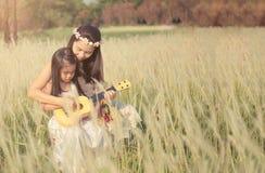 A menina é com sua mãe ao prado exterior na natureza no dia ensolarado foto de stock royalty free
