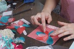 A menina é contratada em fazer cartões em casa Usando o papel, o laço, a trança e os outros materiais imagem de stock royalty free