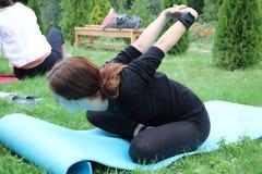 A menina é contratada na ioga da natureza Emparelhe a ioga ou a ioga do acro imagem de stock royalty free