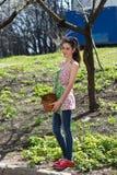 A menina é contratada na remoção de ervas daninhas da grama Imagem de Stock Royalty Free