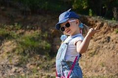 A menina é de jogo e de riso no gramado verde no verão Imagem de Stock Royalty Free